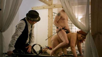 Ulrich Seidl iført tyrolerkostyme instruerer en intim piskescene under innspillingen av sin siste film IM KELLER.